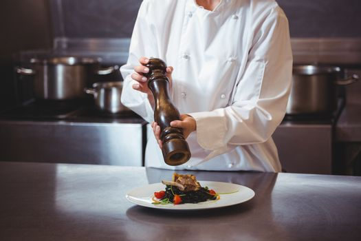 Chef sprinkling pepper on dish