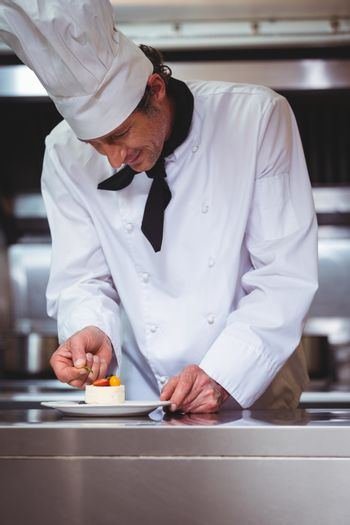 Chef putting finishing touch on dessert