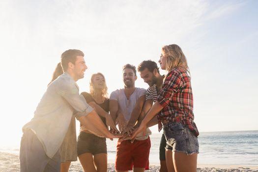 Happy friends gathering hands