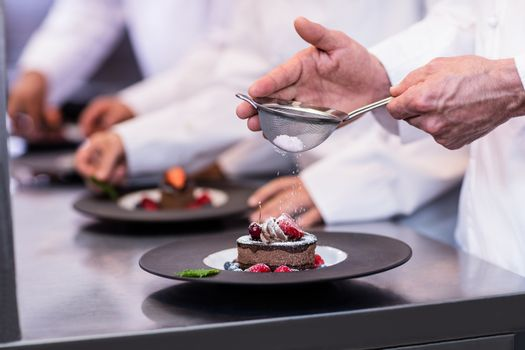 Close-up of chef finishing a dessert plate