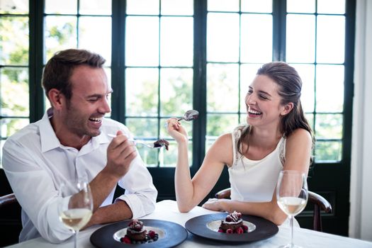 Couple feeding each other and smiling