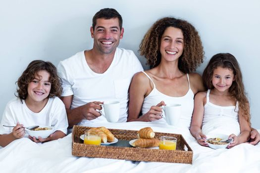 Portrait of family having breakfast in bed at home