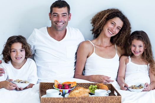 Portrait of a family sitting with breakfast tray in bed at home