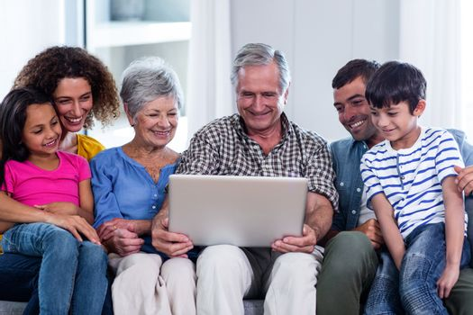 Happy family using laptop on sofa at home