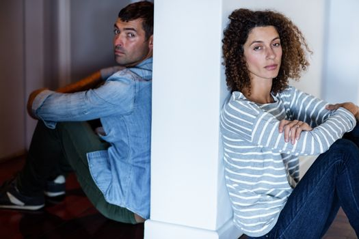Portrait of couple sitting on opposite sides of the wall