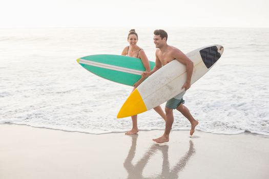 Couple with surfboard running on the beach