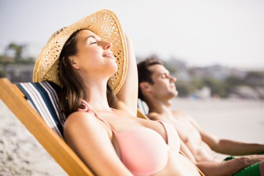 Young couple relaxing on armchair on the beach