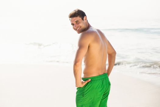 Portrait of man in swim shorts standing on beach