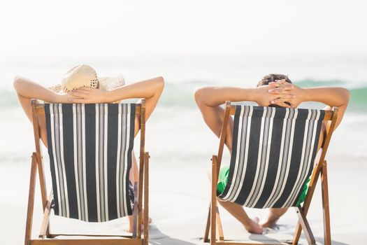Rear view of couple relaxing on the beach