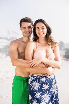 Portrait of happy couple embracing on beach
