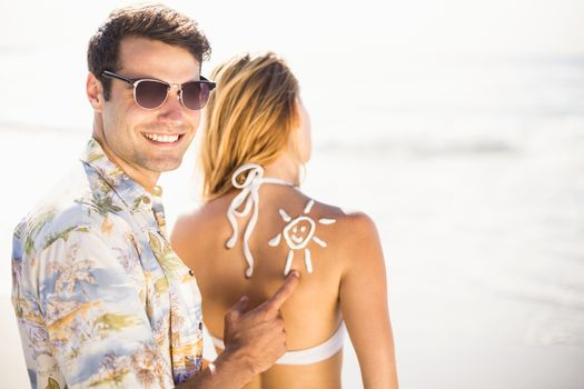 Man making a sun symbol on womans back while applying a sunscreen lotion