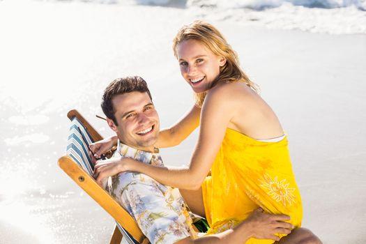 Woman sitting on mans lap at beach