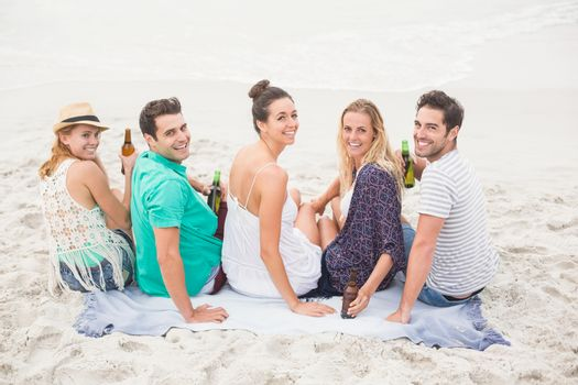 Group of friends sitting side by side on the beach with beer bottles
