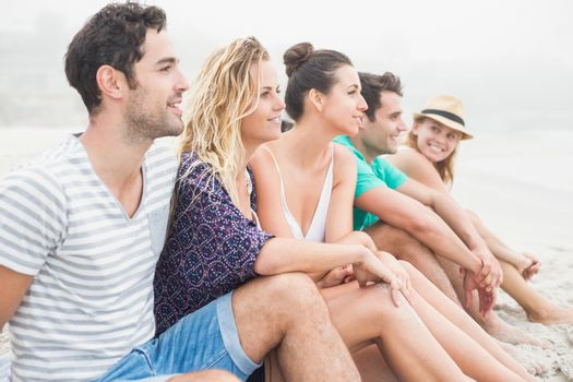 Group of friends sitting side by side on the beach
