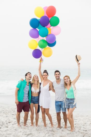 Group of friends standing on the beach with balloons