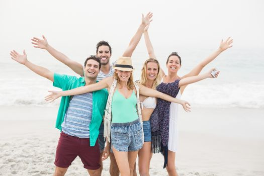 Group of happy friends standing on the beach