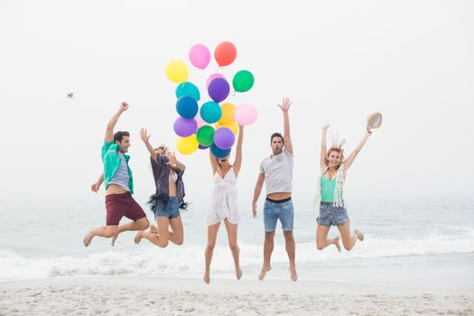 Group of friends jumping on the beach with balloons