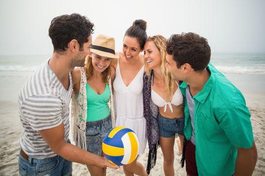 Group of friends with beach ball having fun on the beach