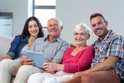 Portrait of happy family sitting on sofa and using a digital tablet in living room