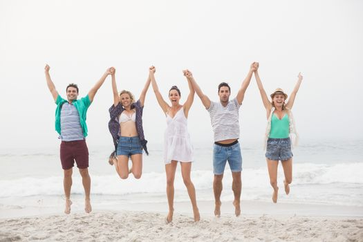 Portrait of friends holding hands and jumping on the beach