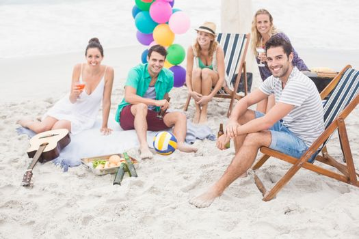 Group of friends with drinks having fun together on the beach