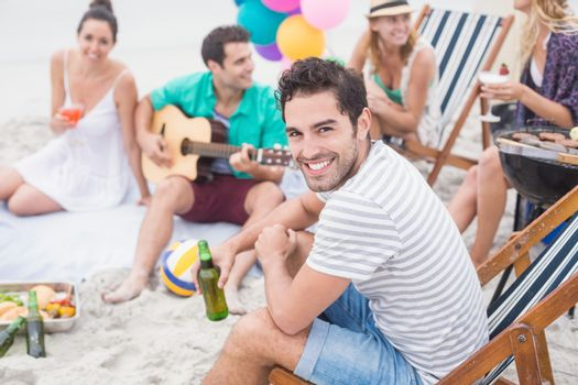 Happy man holding beer and smiling while sitting with his friends
