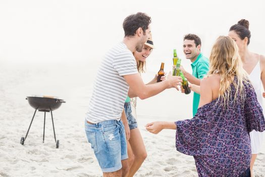 Group of friends dancing on the beach with beer bottles