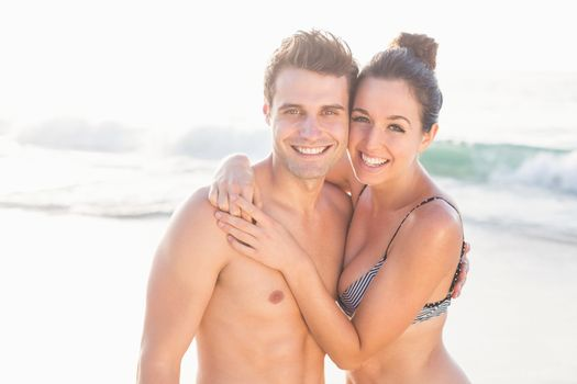 Portrait of happy couple embracing on the beach