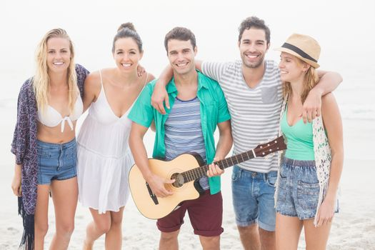Group of friends standing on the beach with a guitar