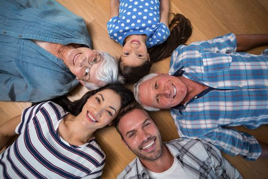 Happy family lying on wooden floor at home