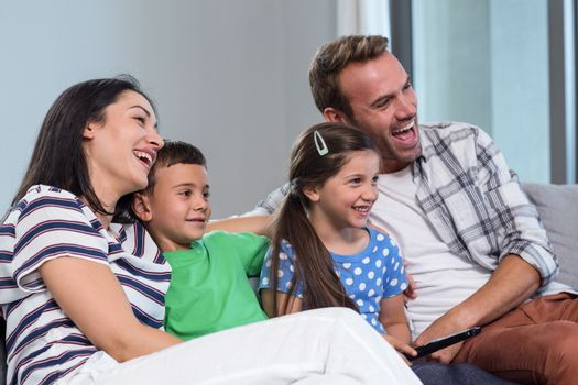 Happy family watching television with their two children sitting on a sofa in the living room