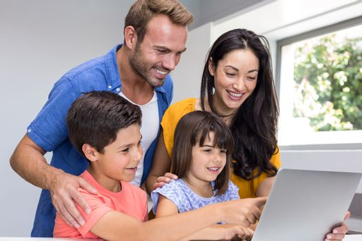 Happy family interacting using laptop in their living room