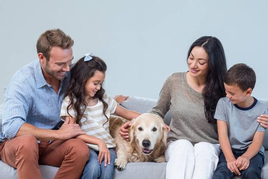 Family petting dog in living room