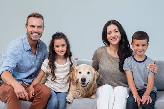 Portrait of family sitting on sofa with dog in living room