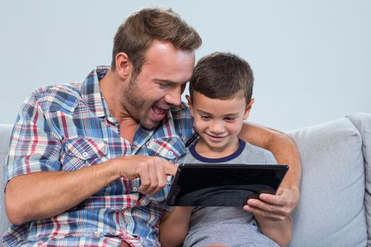 Father and son sitting on sofa and using digital tablet in living room