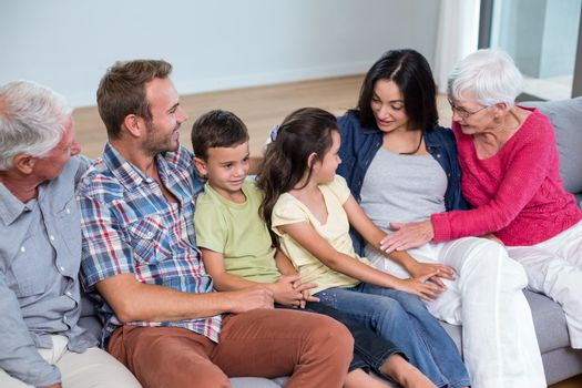 Family sitting on sofa and interacting with each other in living room