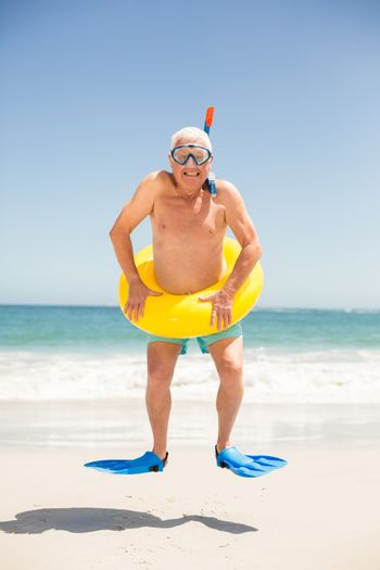 Senior man with swimming ring and flippers jumping