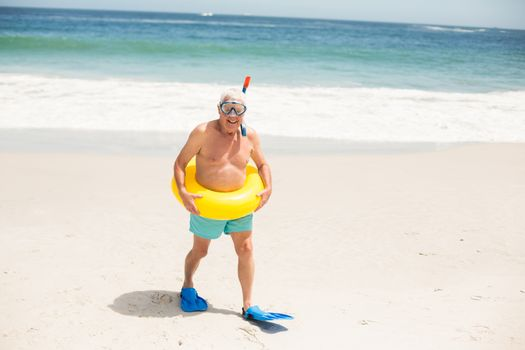 Senior man with swimming ring and flippers at the beach