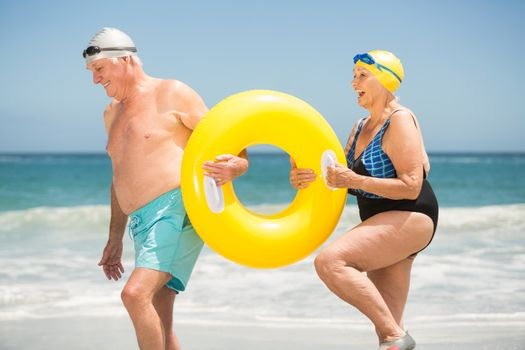 Senior couple with swimming ring at the beach