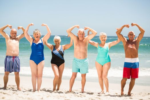 Seniors posing with muscles at the beach