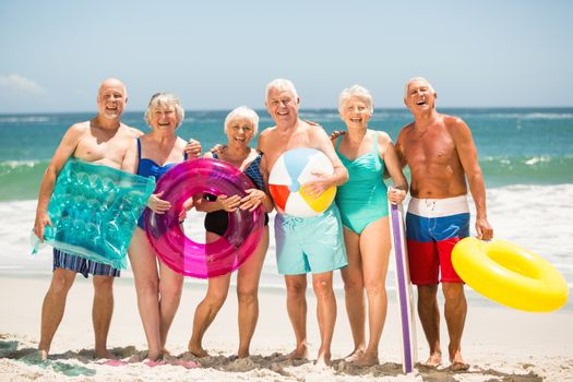 Seniors standing in a row at the beach on a sunny day