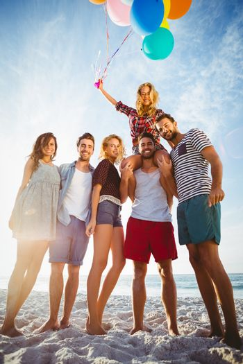 Friends posing with balloon on sand