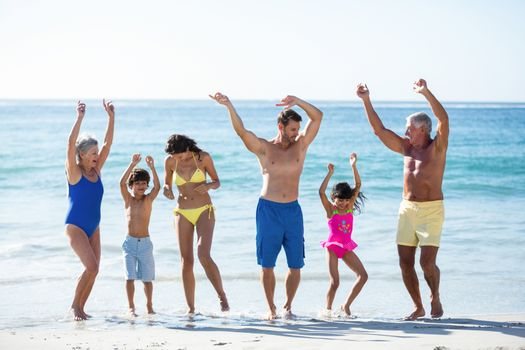 Happy family dancing on the beach