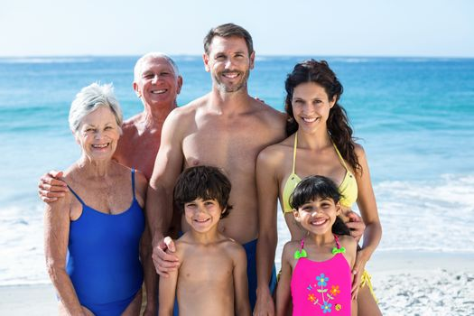 Cute multi generation family posing on the beach