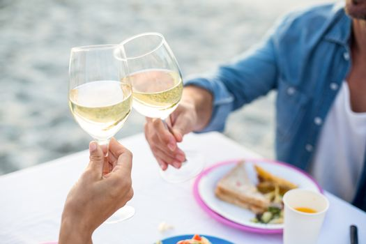 Close up of a couple toasting with white wine