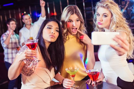 Friends taking a selfie in a club