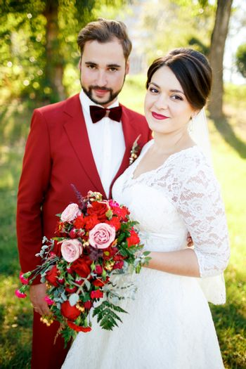 Portrait of the newlyweds couple outdoors, summer, vertical. Marsala decoration style.