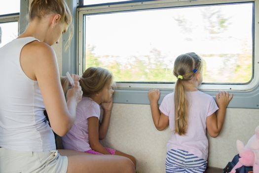 two girls looking out of the window while sitting in an electric train, a young mother combing long hair of one of them
