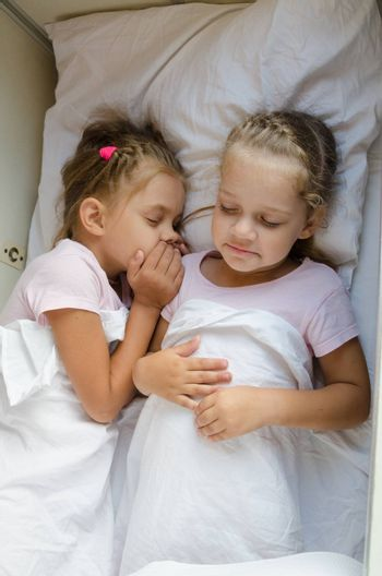 Two little girls sister sleep on a cot in a train