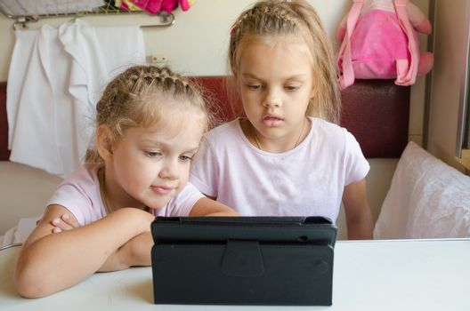 Two girls sisters sitting in the train watching cartoon Tablet PC